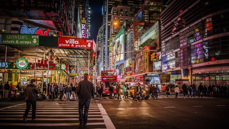 纽约,美国- 2012年, 12月23日:在时代广场附近的区域在晚上 时代广场是一个主要商业交叉点和邻居 免版税库存图片