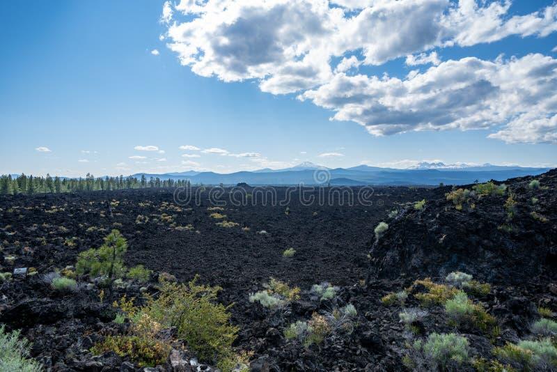 纽贝里全国火山的纪念碑的熔岩土地在中央俄勒冈 小瀑布山脉的看法在背景中 免版税库存图片