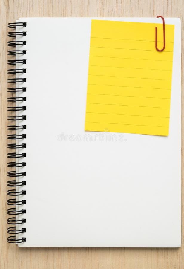 黄线备忘录纸在开放笔记本截去了 免版税库存图片