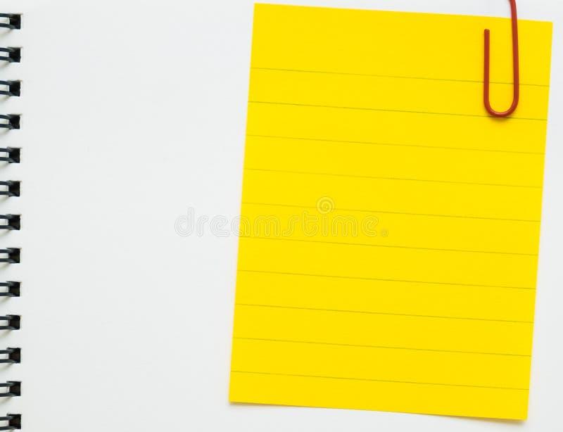 黄线备忘录纸在白色笔记本截去了 免版税库存照片