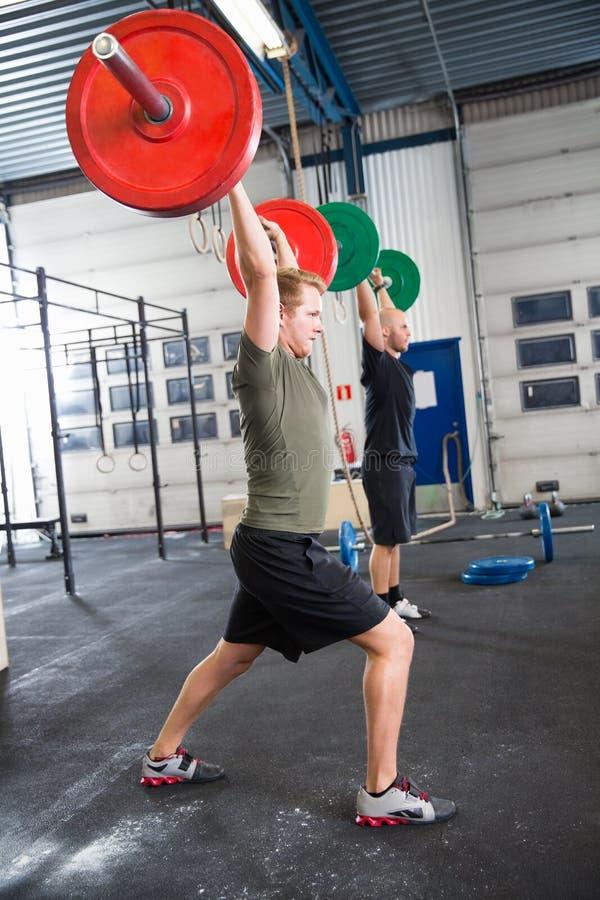练习在健身俱乐部的男性运动员举重 库存图片