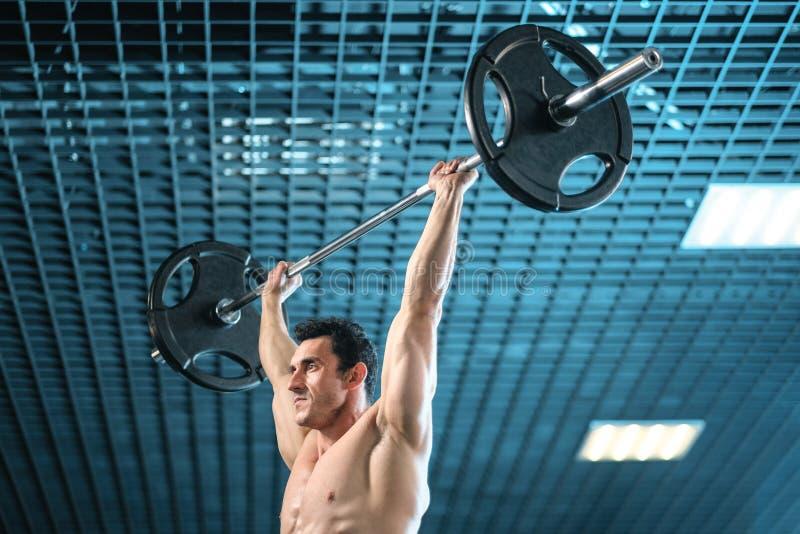 练习大量的杠铃举重的赤裸上身的被聚焦的爱好健美者在健身房 免版税库存照片