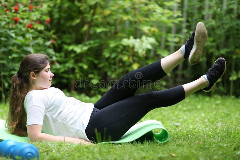 练完火车后,少女用哑铃躺在健身抹布上疲惫 免版税库存照片