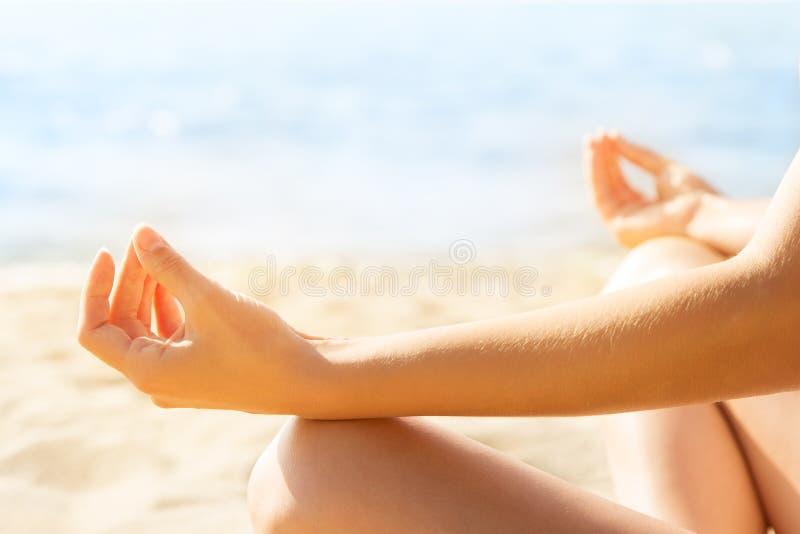 练瑜伽,放松女性坐在海滩上,双手集中 库存照片