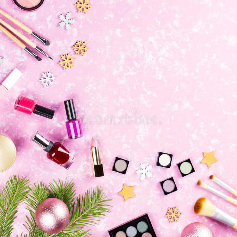 组成化妆用品和圣诞装饰在艺术性的桃红色背景,拷贝空间,顶视图 图库摄影