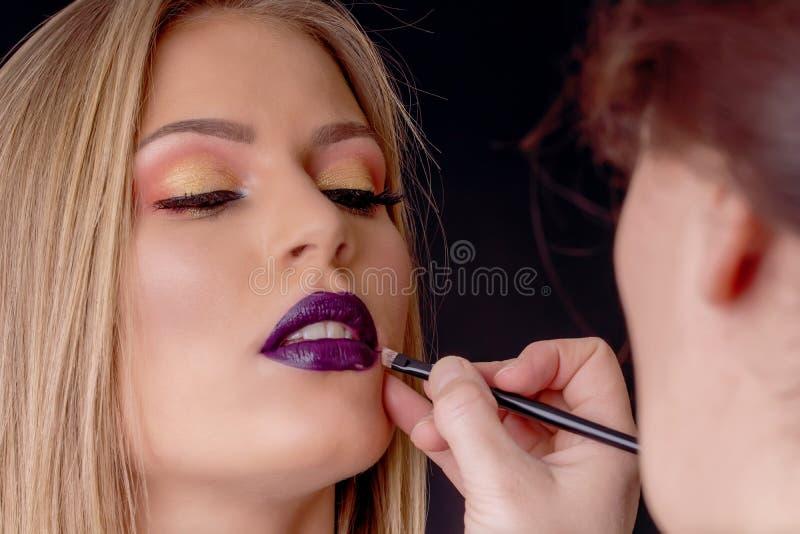 组成在过程,化妆师中应用唇膏,绘嘴唇 图库摄影
