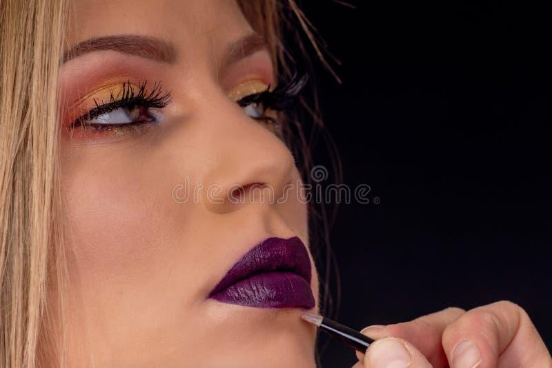 组成在过程,化妆师中应用唇膏,绘嘴唇 免版税库存照片