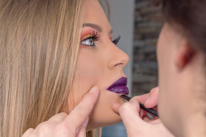 组成在过程,化妆师中应用唇膏,绘嘴唇 库存照片