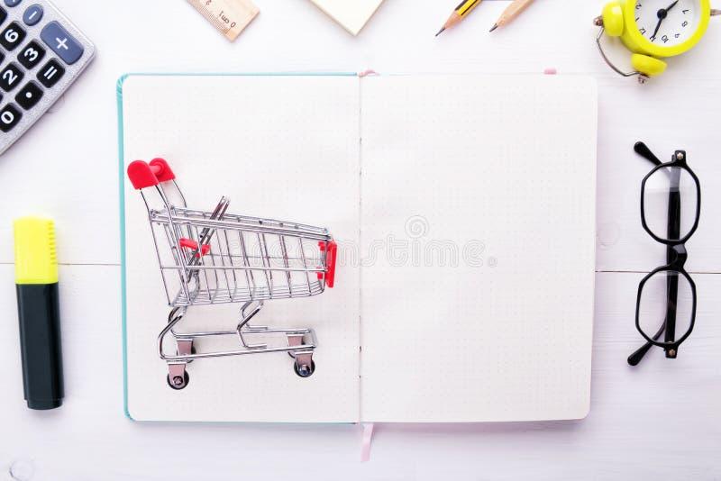 组织您的购物清单:在白干净的笔记本或计划者的小的杂货台车有在一白色木的文具的 免版税库存照片