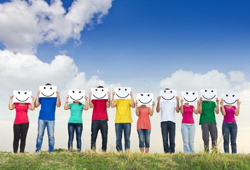 组青年人与面带笑容的藏品纸张 免版税图库摄影
