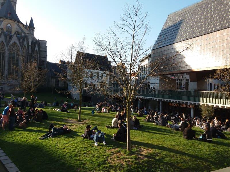 绅士,比利时03 25 2017群人坐草在多功能城市亭子Stadshal附近 免版税库存照片