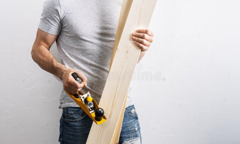 细木工技术:一个人拿着一个大黄色飞机和轻的委员会 库存图片