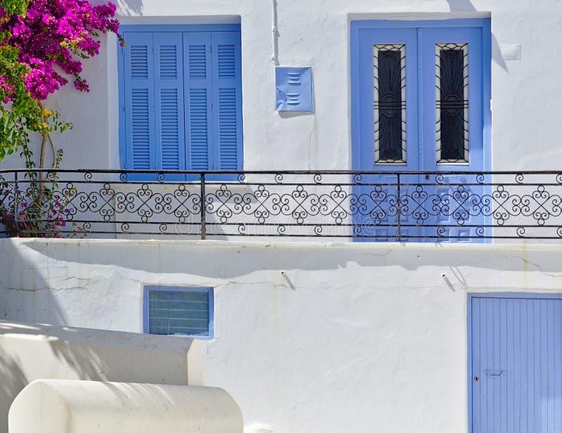 细节与蓝色窗口和门,充满活力的九重葛和阳台有金属栏杆的,蒂诺斯岛的美好的白色房子关闭 免版税库存照片