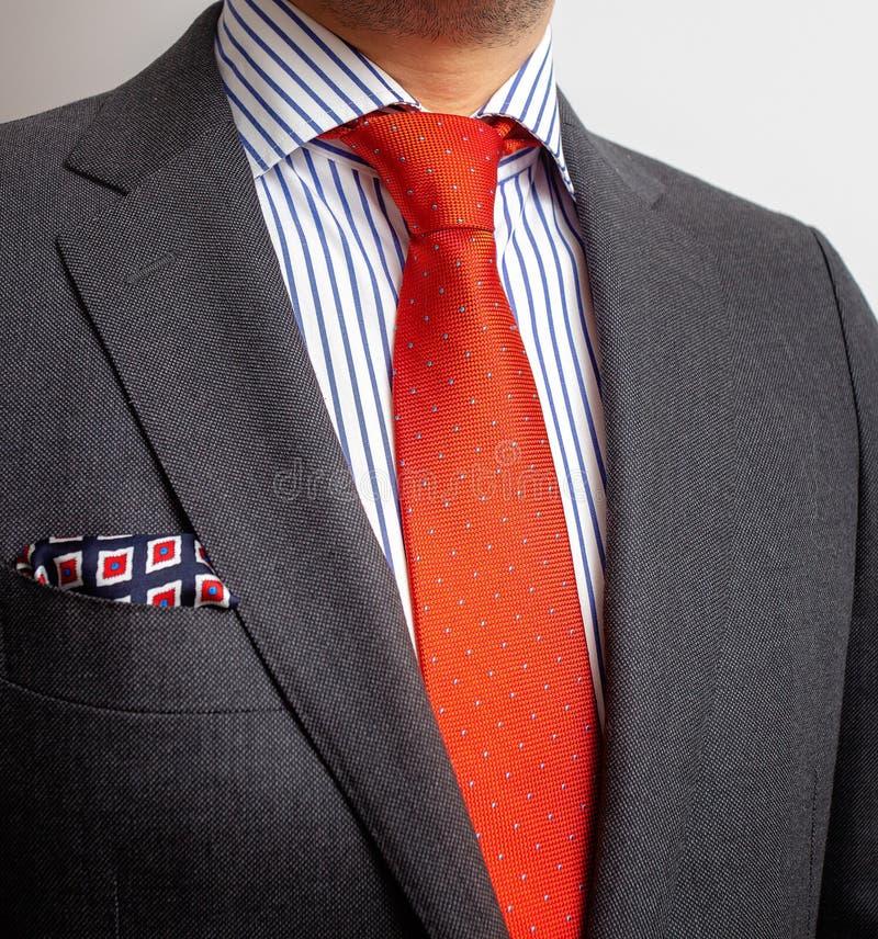 细节特写镜头-夹克人的、衬衣有橙色领带的和口袋正方形 免版税库存照片