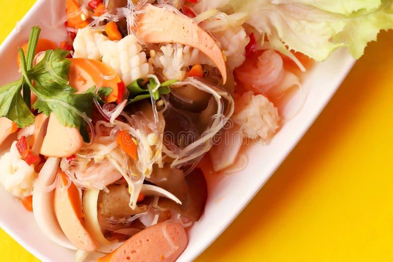 细面条和海鲜顶视图辣沙拉的关闭在白色板材在黄色背景,泰国食物伍恩参议员 库存照片