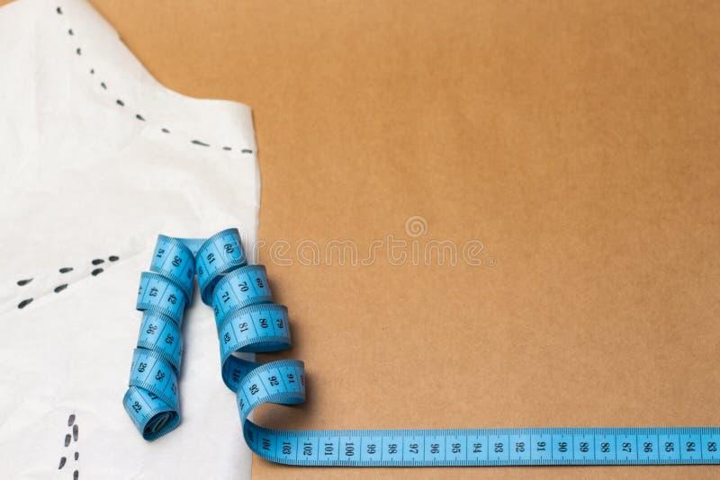 织品片断与鞋带、测量的磁带和色的螺纹的在牛皮纸背景 免版税库存照片