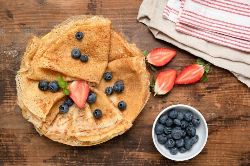 绉纱、稀薄的薄煎饼或者俄国俄式薄煎饼用新鲜的莓果 图库摄影