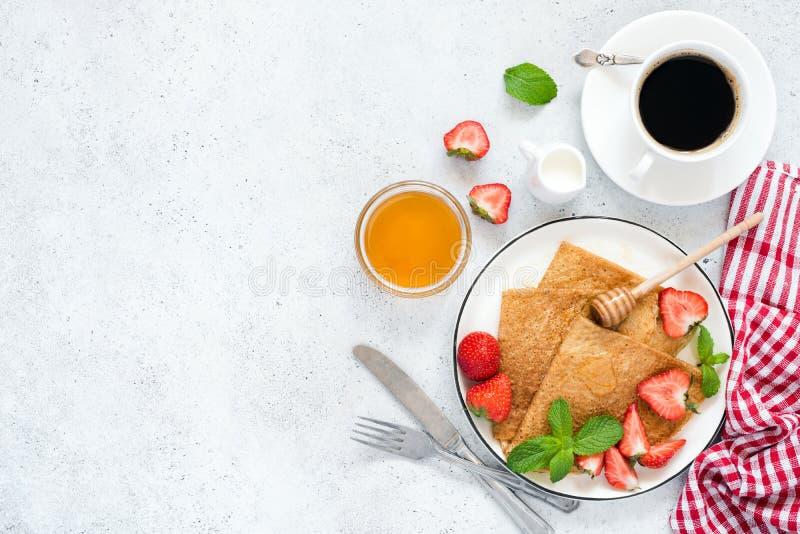 绉纱、稀薄的薄煎饼或者俄式薄煎饼用草莓,蜂蜜,咖啡 免版税库存图片