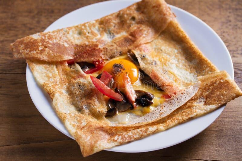 绉纱、稀薄的薄煎饼用乳酪,鸡蛋、蕃茄和蘑菇 库存图片