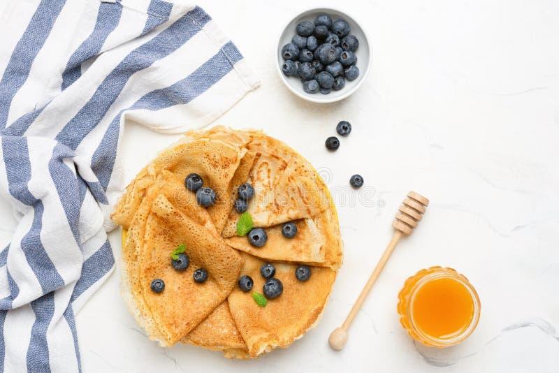 绉纱或俄式薄煎饼用新鲜的莓果和蜂蜜 库存照片