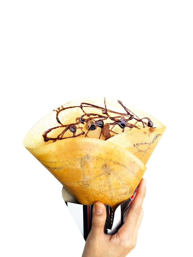 绉纱用早餐或点心的巧克力汁 食物绉纱烘烤了 妇女是拿着自创布朗薄煎饼用谷物的手 免版税库存图片