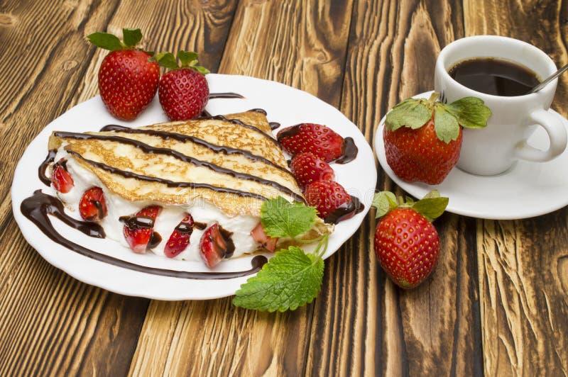 绉纱用香蕉、巧克力和草莓与咖啡 免版税图库摄影