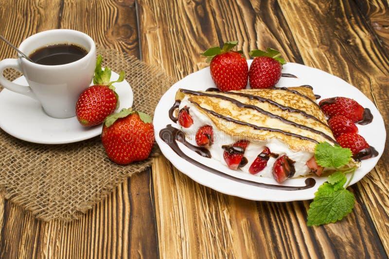绉纱用香蕉、巧克力和草莓在木背景,薄煎饼 免版税库存图片