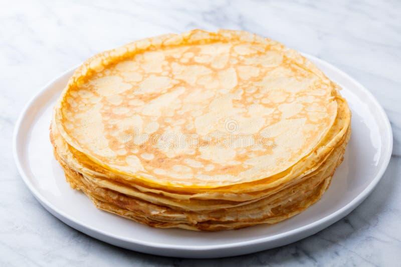 绉纱,稀薄的薄煎饼用在一块白色板材的蜂蜜 r ?? 图库摄影