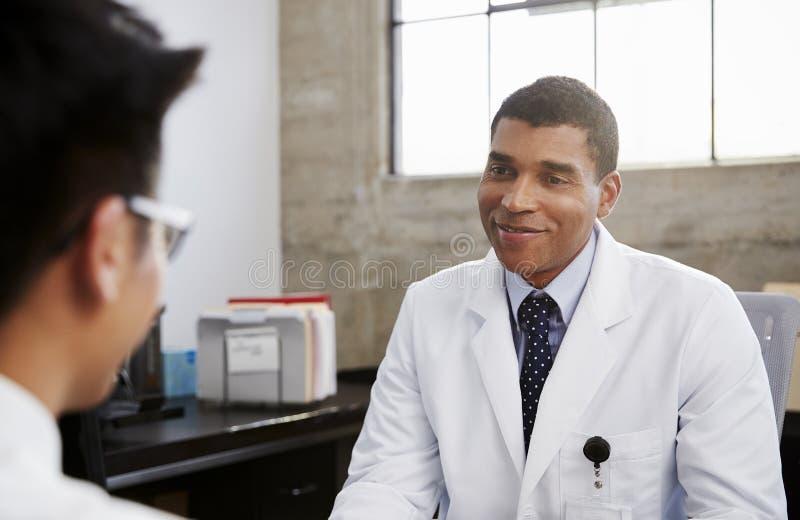 经与患者磋商的微笑的混合的族种男性医生 库存照片
