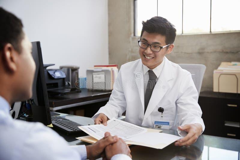 经与男性患者磋商的愉快的亚裔男性医生 免版税库存图片