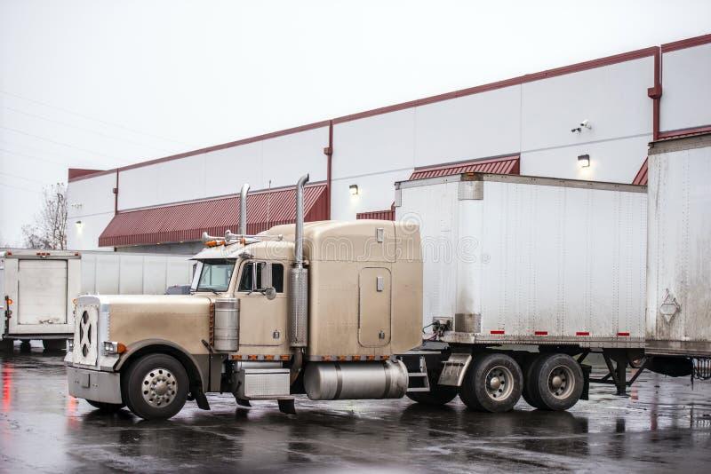 经典大半半船具卡车装载的货物在行的仓库船坞与在湿停车场的另一辆拖车 免版税库存照片