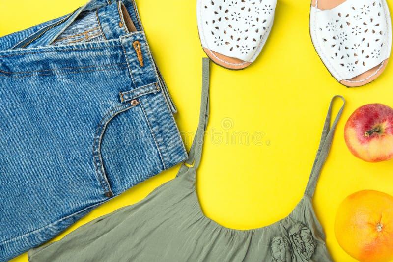 经典妇女牛仔裤牛仔布短裤用在黄色背景的边缘橄榄色的颜色无袖衫Espandrille凉鞋苹果计算机葡萄柚 免版税图库摄影