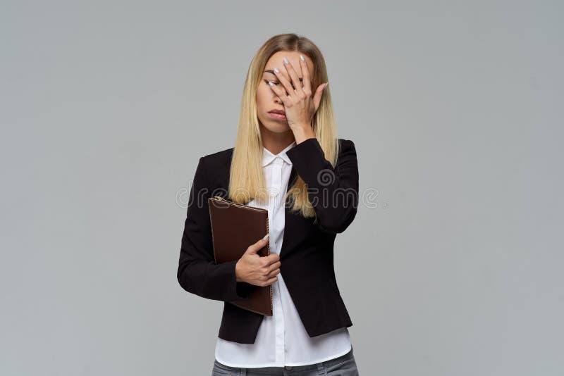 经典礼服的年轻女商人夫人用棕榈不倦地盖她的面孔 在灰色被隔绝的背景的演播室画象 库存图片