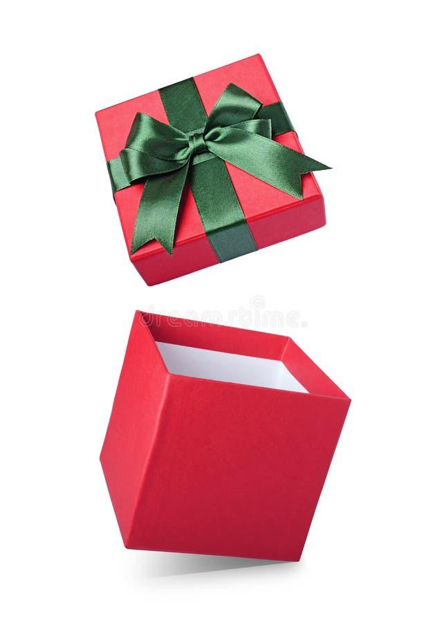 经典红色有绿色缎弓的飞行开放礼物盒 库存图片