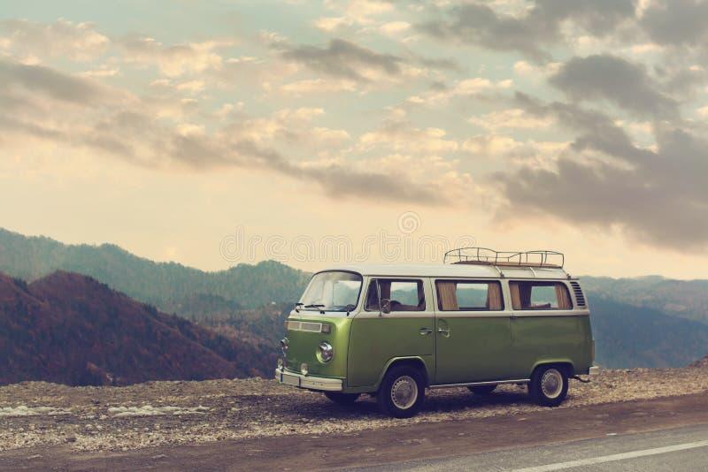 经典绿色葡萄酒在路停放的露营者货车 免版税库存图片