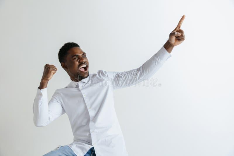 经典衬衣的英俊的美国黑人的人微笑着,看照相机并且指向  免版税库存照片