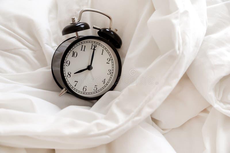 经典闹钟在床,早晨惯例的概念上 免版税库存照片