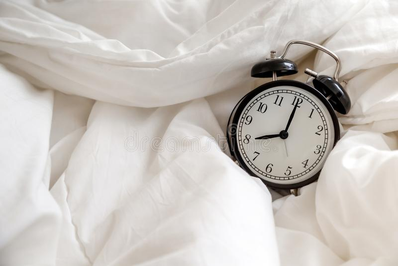 经典闹钟在床,早晨惯例的概念上 免版税图库摄影
