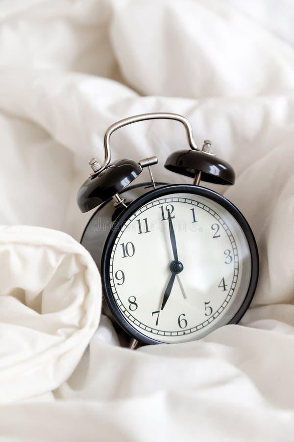 经典闹钟在床,早晨惯例的概念上 库存照片