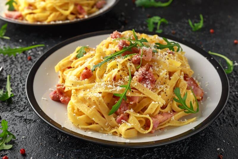 经典Carbonara面团、意粉有pancetta的,烟肉、鸡蛋、帕尔马干酪和绿色芝麻菜 库存照片