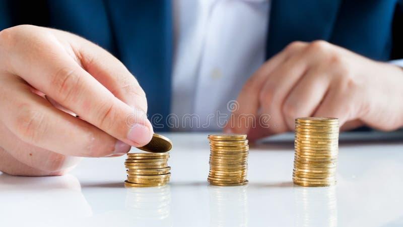 经济成长和稳定概念性照片  投入硬币的人在堆 库存照片
