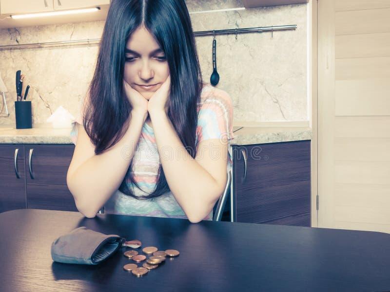 经济的概念,有长的黑发的一名年轻失望的妇女,在一个老空的钱包旁边坐与 免版税图库摄影