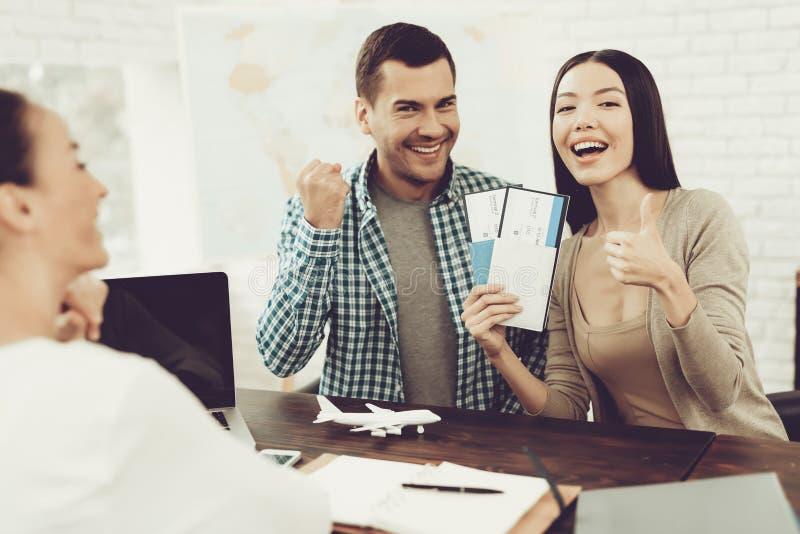 经理在旅行社中卖了到夫妇的票 免版税库存图片