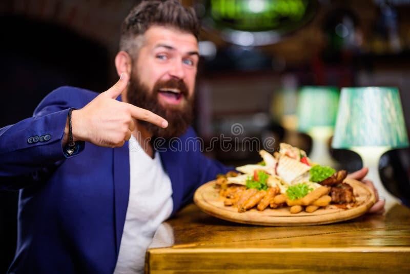 经理正装坐在酒吧柜台 人接受了与油煎的土豆的膳食炸鱼排肉 可口膳食 享受膳食 库存图片