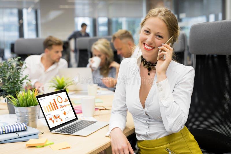 经理研究膝上型计算机和谈话在电话 图库摄影