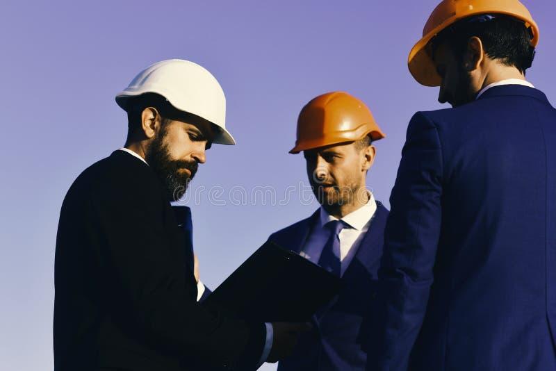 经理穿巧妙的衣服、领带和安全帽在蓝天背景 建设者举行夹子文件夹 修造和 库存图片