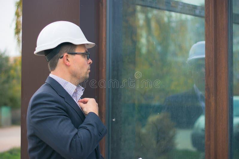经理穿着巧妙的衣服、领带和安全帽和手表在玻璃镜子 建筑师控制工作 免版税库存图片