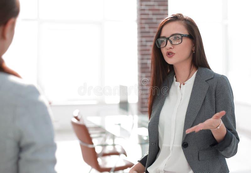 经理谈话与一个客户身分在办公室 库存照片