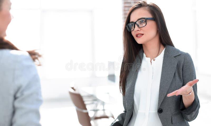 经理谈话与一个客户身分在办公室 免版税库存图片