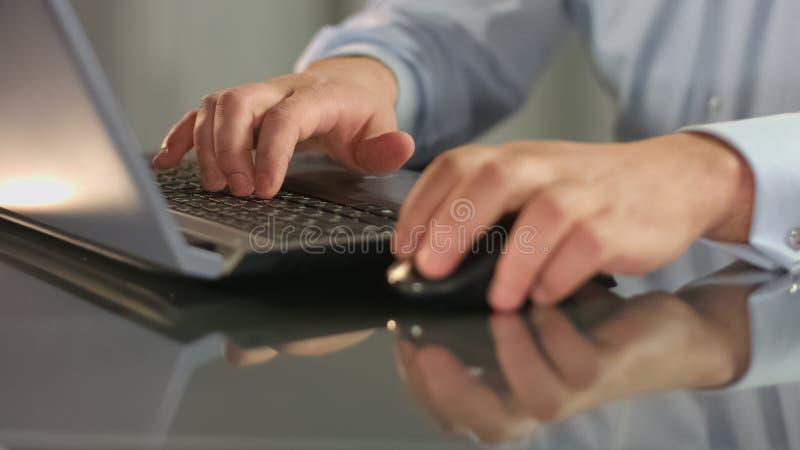 经理键入的膝上型计算机键盘藏品老鼠,浏览互联网网站应用 免版税库存图片
